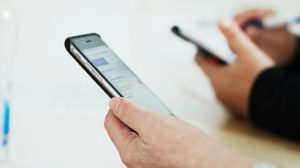 En äldre persons hand håller en mobiltelefon
