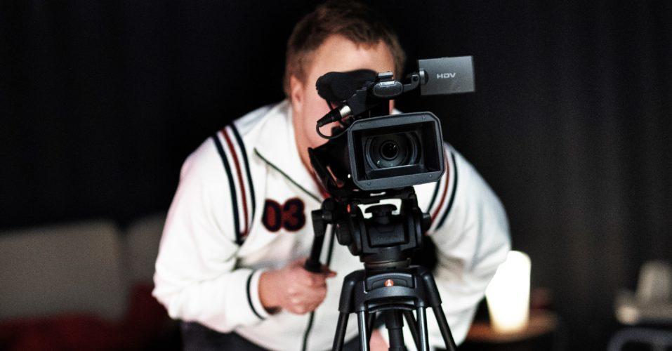 En person filmar med filmkamera.